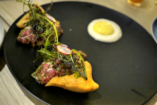 Steak and oyster tartare with champagne sabayon and bone marrow beignets