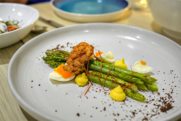 Asparagus with deviled egg purée, fried oyster and black bread