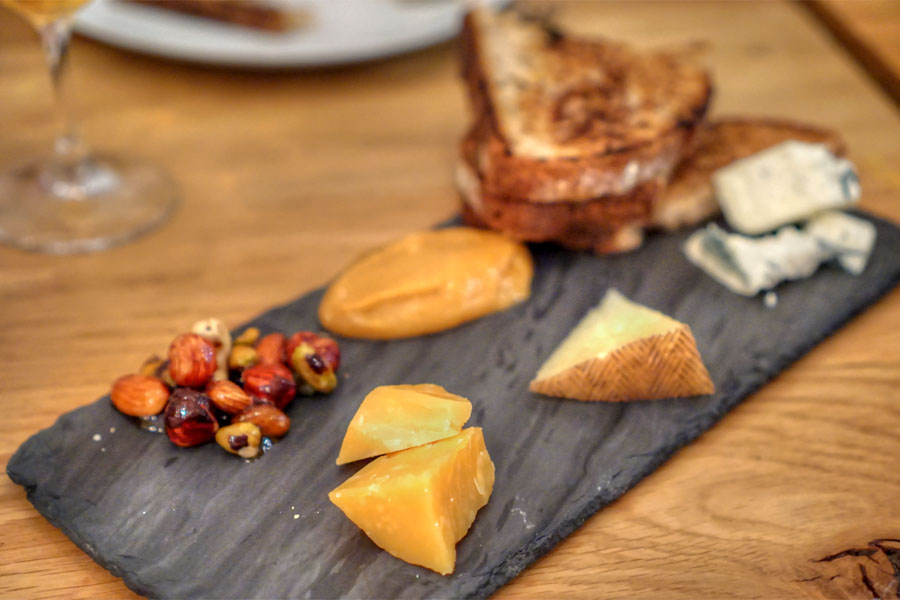 selection of cheeses with ginger-persimmon jam, nuts, honey, and griddled bread